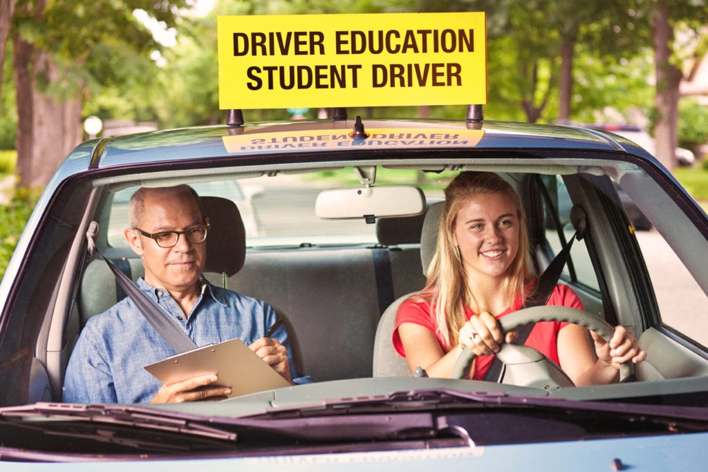Teenager in Drivers's License Exam with Examiner in Car