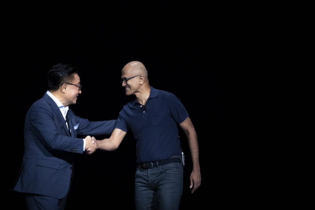 DJ Koh, president and CEO of Samsung Electronics, shakes hands with Satya Nadella, CEO of Microsoft.